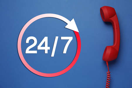 24/7 hotline service. Red handset on blue background, top view
