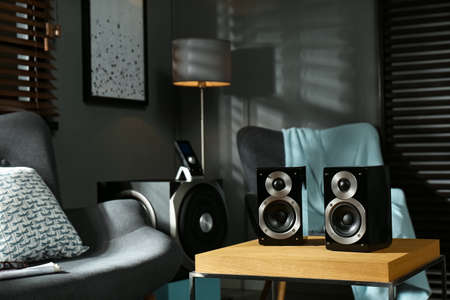 Modern audio speaker system on wooden table in living room Banque d'images