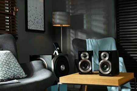 Modern audio speaker system on wooden table in living room Banco de Imagens