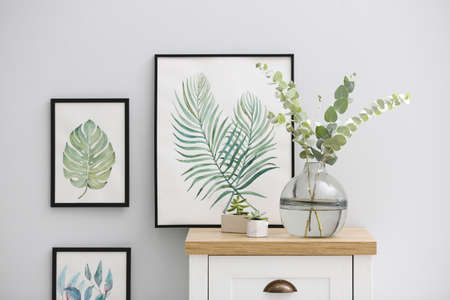 Vase with fresh eucalyptus branches on cabinet in room. Interior design