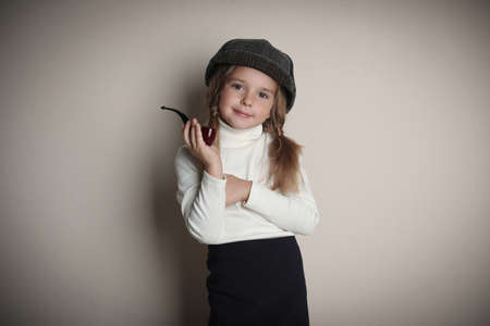 Cute little child in hat with smoking pipe playing detective on beige background