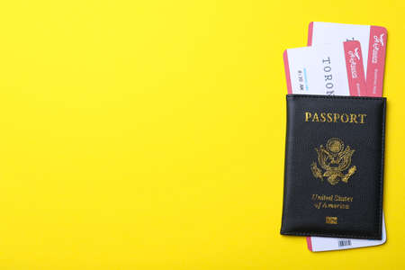 Passport with avia tickets on yellow background, top view and space for text. Travel agency concept