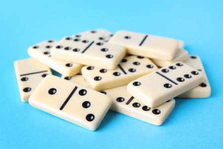 White domino tiles on turquoise background, closeup