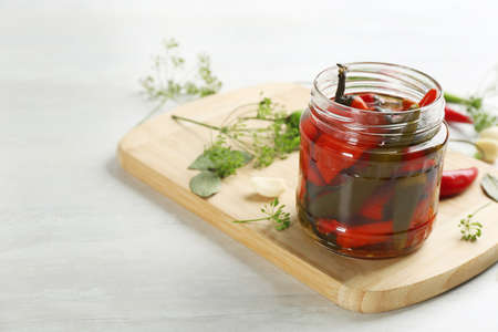 Glass jar of pickled chili peppers and ingredients on white table. Space for text