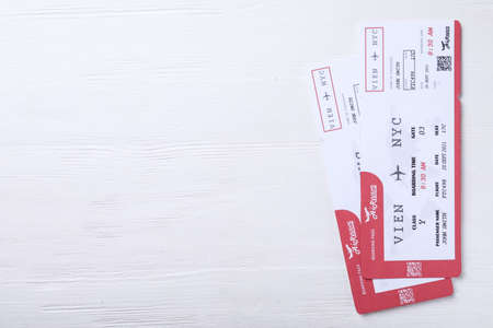 Tickets on white wooden table, flat lay with space for text. Travel agency concept