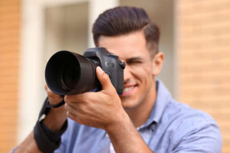 Photographer taking picture with professional camera outdoors, focus on device