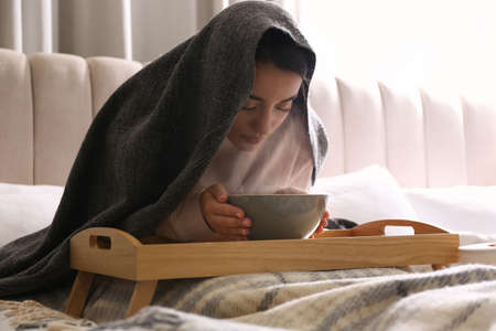 Woman with plaid doing inhalation above bowl on bed Foto de archivo