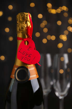 Heart shaped greeting card with phrase I Love You tied to bottle of champagne against blurred lights, closeup
