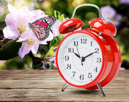 Red alarm clock on wooden table. Daylight saving time (Spring forward)