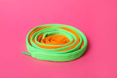 Mint and orange shoe laces on pink background Standard-Bild