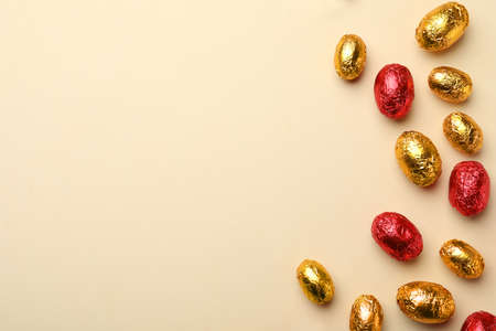 Chocolate eggs wrapped in red and golden foil on beige background, flat lay. Space for text