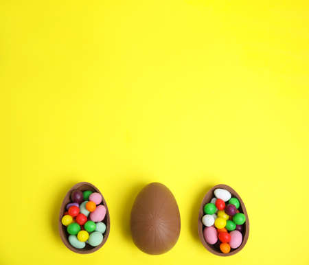 Tasty chocolate eggs with colorful candies on yellow background, flat lay. Space for text
