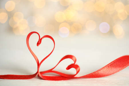 Two hearts made of red ribbon on table against blurred lights, space for text. St. Valentine's day card