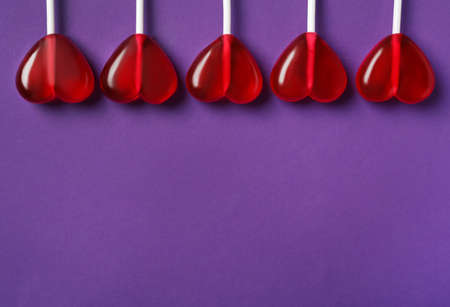 Sweet heart shaped lollipops on purple background, flat lay with space for text. Valentine's day celebration
