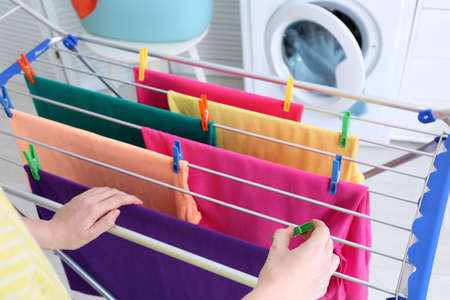 Woman hanging clean laundry on drying rack indoors, closeup