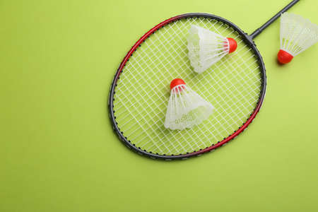 Badminton racket and shuttlecocks on light green background, flat lay. Space for text