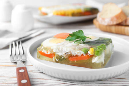Delicious fish aspic served on white wooden table, closeup