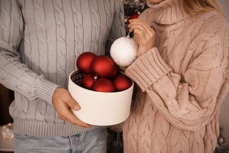 Couple with box of Christmas balls indoors, closeup