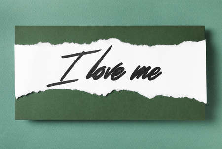 Paper with handwritten phrase I Love Me on green background, top view