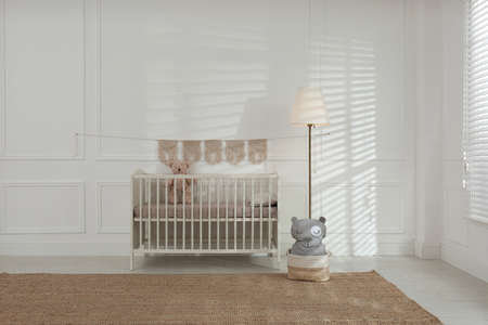 Cute baby room interior with comfortable crib and teddy bear Stockfoto