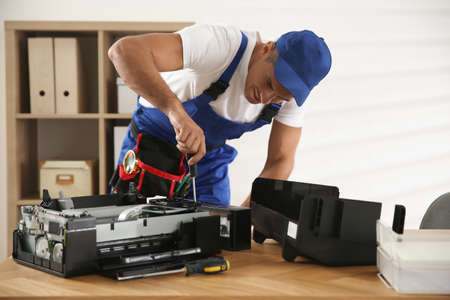 Repairman with screwdriver fixing modern printer in office Stock Photo