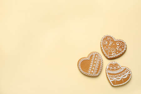 Tasty heart shaped gingerbread cookies on yellow background, flat lay. Space for text