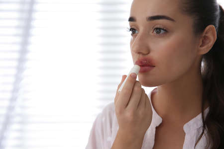 Young woman with herpes applying lip balm against light background. Space for text