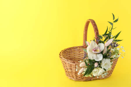 Wicker basket decorated with beautiful flowers on yellow background, space for text. Easter item