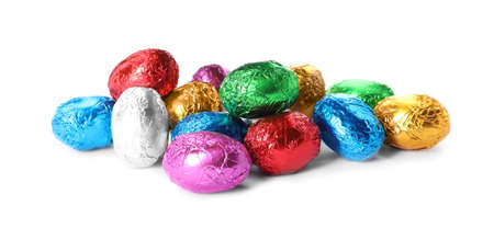 Chocolate eggs wrapped in colorful foil on white background