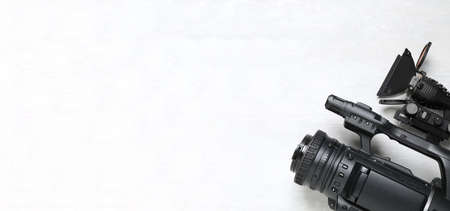 Modern video camera with flashlight on white background, top view. Space for text