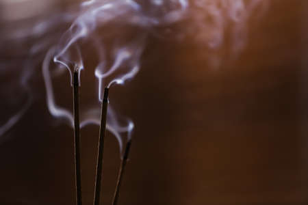 Incense sticks smoldering on blurred background, closeup. Space for text