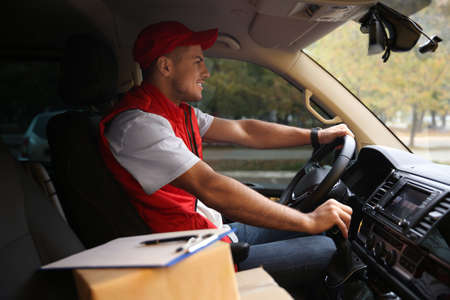 Courier in uniform on driver's seat of car