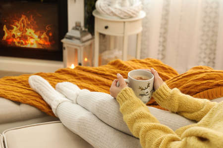 Woman with cup of hot drink resting on sofa near fireplace in living room, closeup
