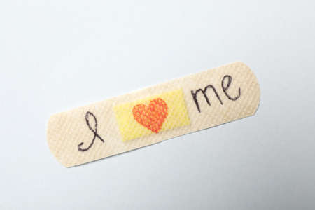 Sticking plaster with phrase I Love Me on white background, top view