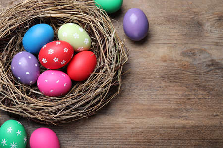 Colorful eggs and nest on wooden background, flat lay with space for text. Happy Easter