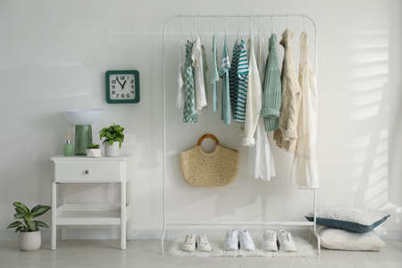 Dressing room interior with clothing rack and nightstand