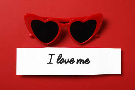 Paper with handwritten phrase I Love Me and heart shaped sunglasses on red background, flat lay