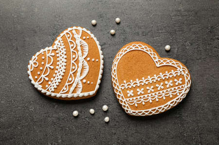 Tasty heart shaped gingerbread cookies on black table, flat lay