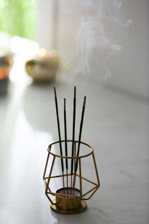 Incense sticks smoldering on table in room Stock Photo