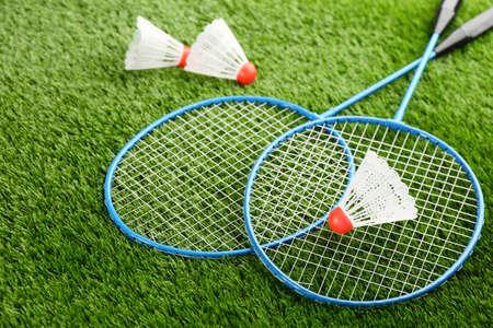 Badminton rackets and shuttlecocks on green grass outdoors
