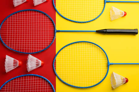 Badminton rackets and shuttlecocks on color background, flat lay