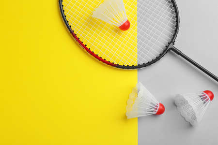 Badminton racket and shuttlecocks on color background, flat lay. Space for text