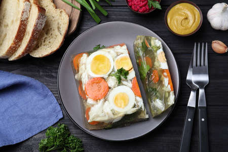 Delicious fish aspic served on black wooden table, flat lay