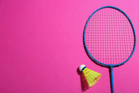 Badminton racket and shuttlecock on pink background, flat lay. Space for text