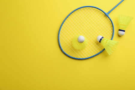 Badminton racket and shuttlecocks on yellow background, flat lay. Space for text