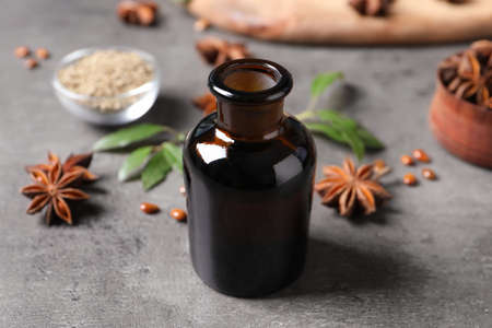 Bottle of essential oil and anise on grey table