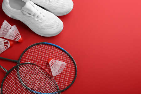 Badminton rackets, shuttlecocks and shoes on red background, flat lay. Space for text