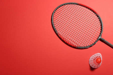 Badminton racket and shuttlecock on red background, flat lay. Space for text