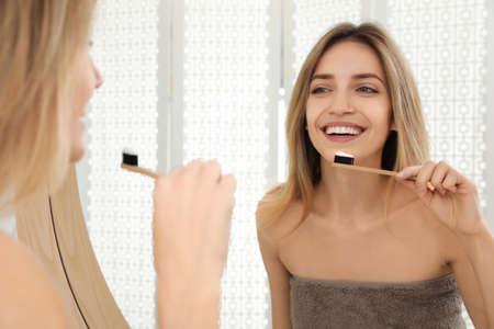 Woman brushing teeth near mirror in bathroom
