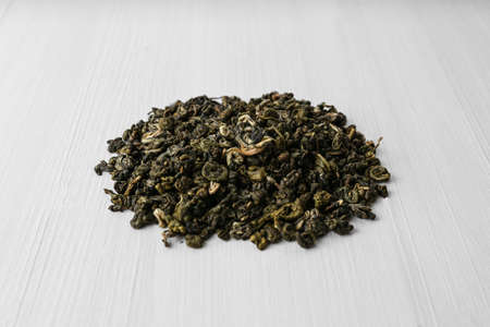 Heap of dry green tea leaves on white wooden table